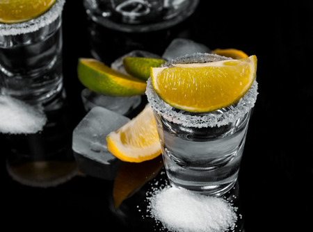 Tequila with lemon or lime and salt on reflex background photo