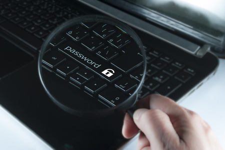 mans hand with magnifying glass above computer keyboard with notice password photo