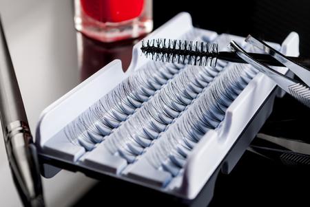 fake eyelashes: Falsy or fake eyelashes sets with tweezers and mascara on black background