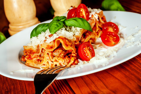 Italian lasagne with tomato and vegetables and chesse on wood table Imagens