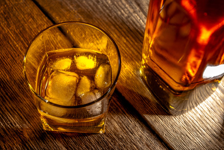 bourbon: Whiskey, bourbon or brown rum with ice on wood table