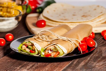 tortilla wrap: Mexican tortilla wrap with meat and vegetables on wood table