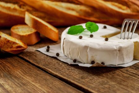 hermelin: French traditional camembert cheese with baguette on wood table