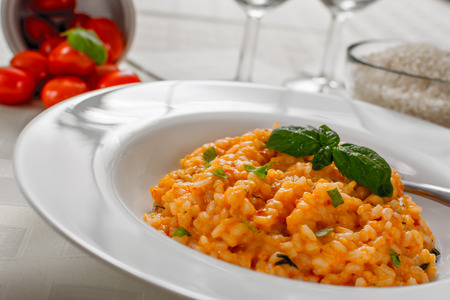 Red risotto with tomato and basil on white plate