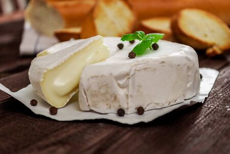 blight: French traditional camembert cheese with baguette on wood table
