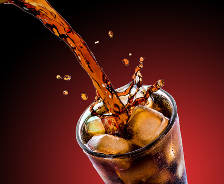 Cola drink splash with ice cube on red background