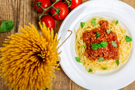 bolognese sauce: Spaghetti with bolognese sauce and basil on wood table