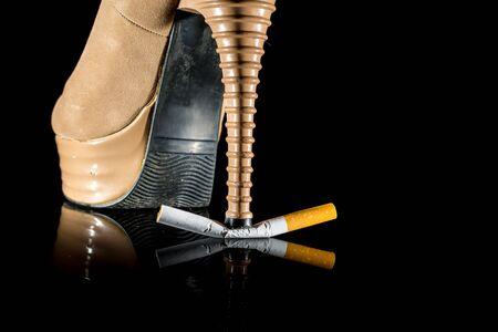 health risk: Woman shoe or heel break cigarette on black background