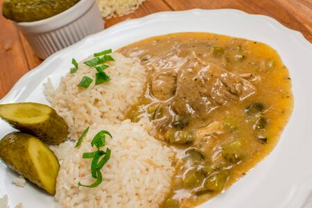 gherkin: Czech traditional food Znojmos sauce with gherkin and pork meat and rice on wood table