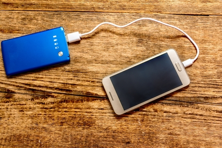 Mobile phone charging by power bank on wood table