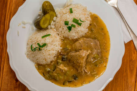znojmo: Czech traditional food Znojmos sauce with gherkin and pork meat and rice on wood table
