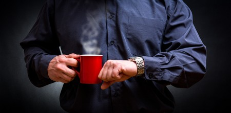 looking at watch: Business man with  newspaper drinking hot coffee and looking watch Stock Photo