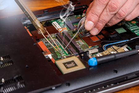 Man fixing damaged memory computer or laptop with soldering iron