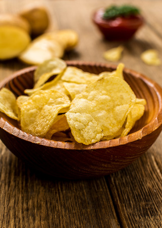 nosh: Salty potato chips snack with tomato dip on wood table Stock Photo