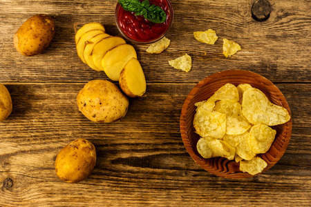 Salty potato chips snack with tomato dip on wood table top view