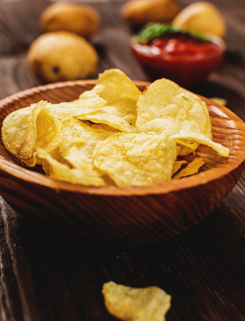 Salty potato chips snack with tomato dip on wood table Stock Photo