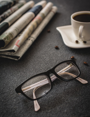 newsprint: Classes and newspaper and cup of coffee on black stone background