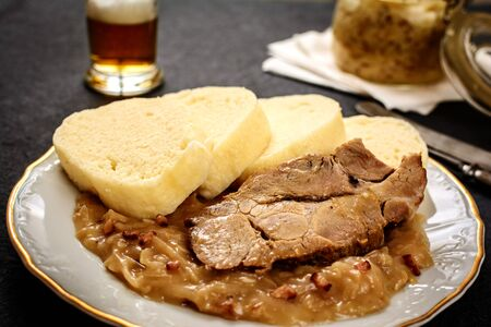 Czech traditional cuisine dumplings cabbage and pork meat and beer  on black stone table Imagens