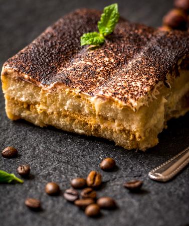 Traditional italian dessert tiramisu on black stone table Stock Photo