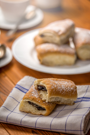 Traditional czech buns with plum jam and coffee on wood table