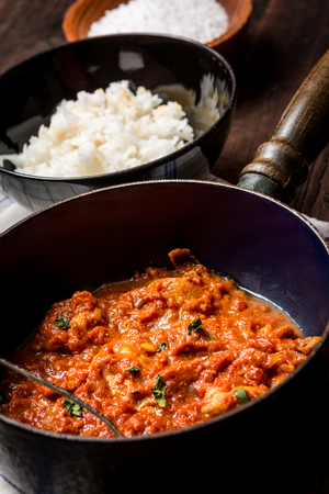 Traditional indian cuisine. Spicy tikka masala with rice on wood table
