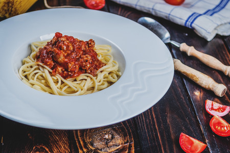 Traditional Italian pasta spaghetti bolognesse with minced meat and tomatoes and raw spaghetti on dark wood table Stockfoto