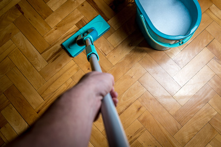 Wiping dirty wooden floor by wet wiper mop, housework. Man cleaning the house. Topview Stock Photo