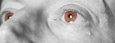 Oko smutnego mężczyzny ze łzową czarno-białą fotografią z brązowymi oczami