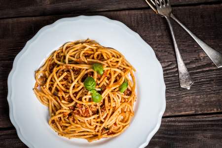Italian spaghetti bolognese. Traditional pasta with bolognese sauce on white plate on wood table top view Zdjęcie Seryjne
