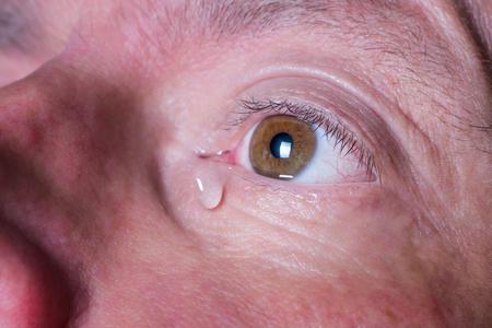 Braunes Auge eines traurigen Mannes mit tränenbraunen Augen Standard-Bild