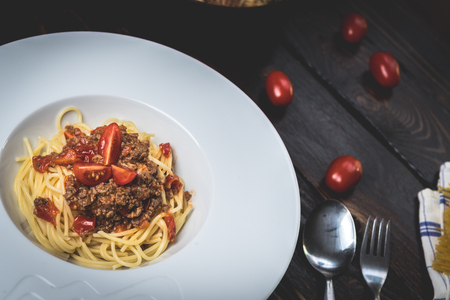 Traditional Italian pasta spaghetti bolognese with minced meat and  tomatoes on dark wood table Archivio Fotografico