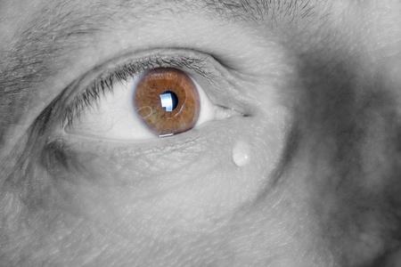 Auge des traurigen Mannes mit Tränenschwarz-Weiß-Fotografie mit farbigen braunen Augen