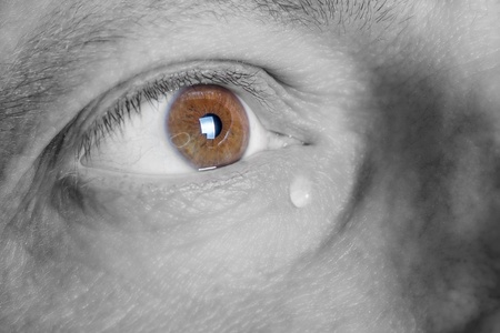 Eye of sad man with tear black and white photography with color brown eyes