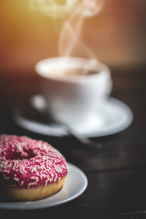 Pink donut with white sprinkle and cup of coffee on wood table