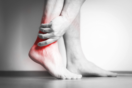 Causian man holds hands to his painful feet, pain in foot.  Black and white photography. red color is area of pain