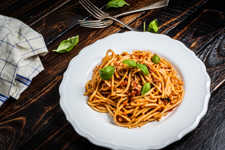 Italian spaghetti bolognese. Traditional pasta with bolognese sauce on white plate on wood table.