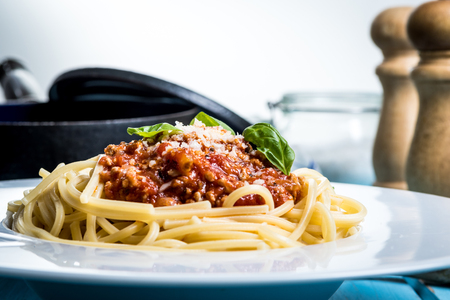 Traditional italian pasta spaghetti bolognese with minced meat, tomato, cheese parmesan and basil on blue wood table Zdjęcie Seryjne