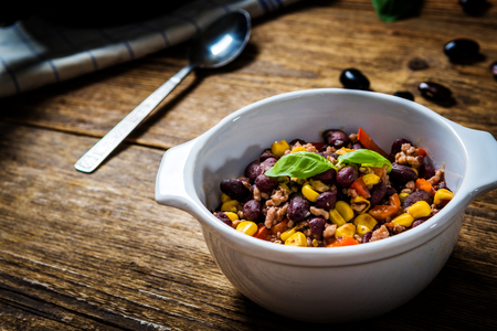 Chili or chilli corn carne. Cooked kidney bean, minced meat, chili, corn and pepper in white bowl  on wood table Imagens