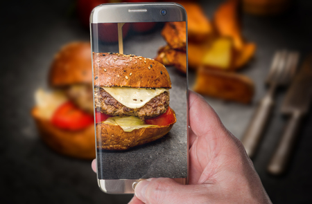 Man taking photo of Traditional Cheeseburger with beef meat and fried potato