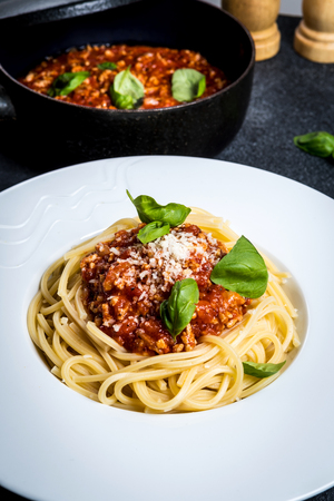 Traditional italian pasta spaghetti bolognese with minced meat, tomato, cheese parmesan and basil on dark stone table