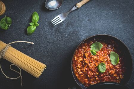 Traditional italian pasta spaghetti bolognese with minced meat, tomato, cheese parmesan and basil on dark stone table top view