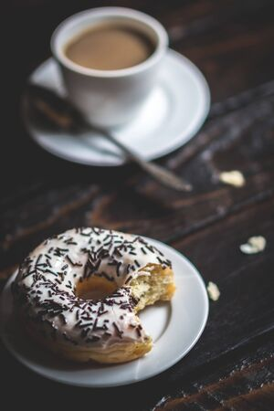 Bite a white donut with chocolate sprinkle and cup of coffee on wood table