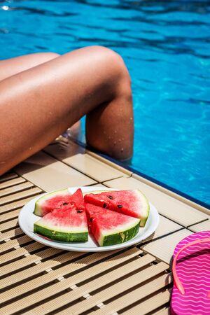Girl eating melon near swimming pool in summer sunny day Foto de archivo