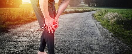Muscle man holds his injured knee on road in  summer sunset. Red color is pain 版權商用圖片