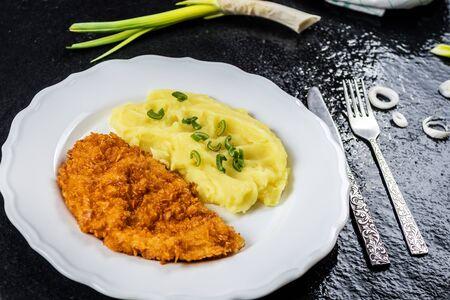 Fried chicken steak or schnitzel with mashed potatoes on black stone table Reklamní fotografie