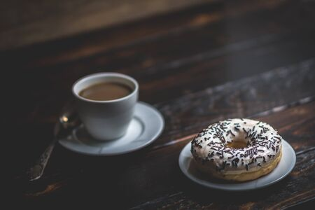 White donut with chocolate sprinkle and cup of coffee on wood table