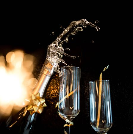 champagne glass with splash on black background - new year celebration Imagens