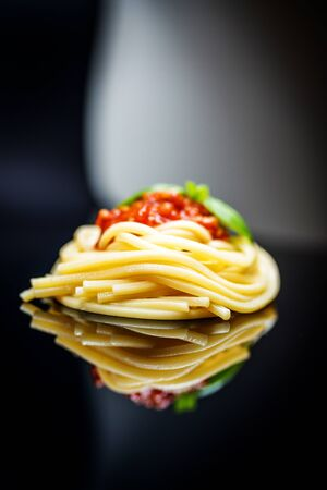Italian pasta spaghetti bolognese with basil on black background