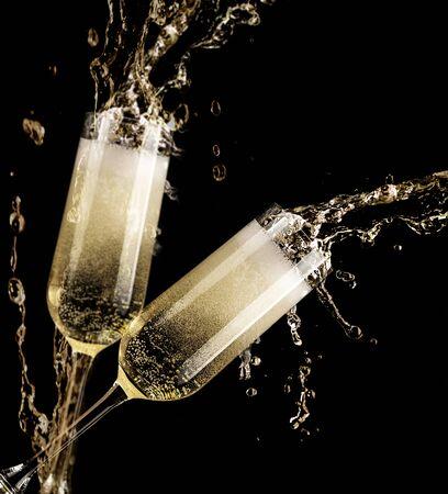 Copa de champán con salpicaduras sobre fondo negro - celebración de año nuevo