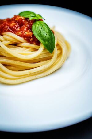 Italian pasta spaghetti bolognese with basil in white plate on black background Фото со стока - 134455885